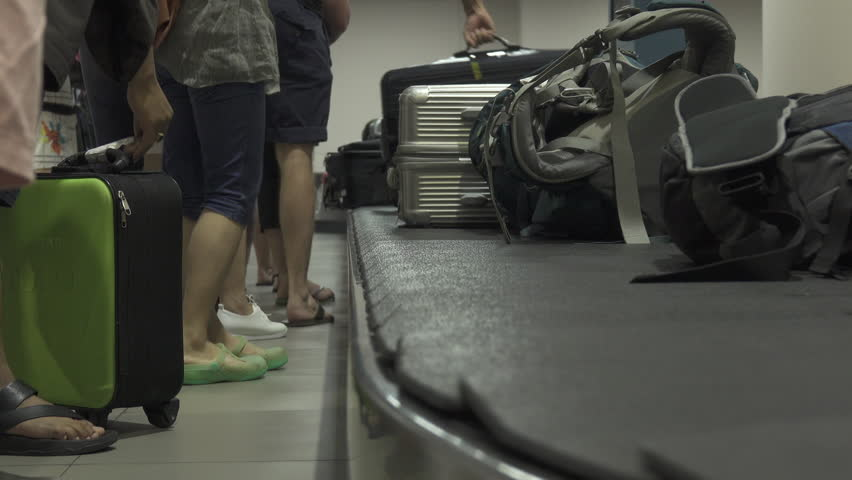 THAILAND AIRPORT March 2018, CLOSE UP: Travelers pick up their luggage off spinning rubber carousel. Unrecognizable people collecting their suitcases after a long flight to Don Mueang airport.