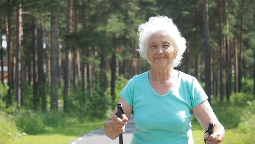 Active Elderly 80 Years Old Woman Training Nordic Walking In Park With Trekking Poles. Hiking Senior Woman Walking Sumer Travelling. Active Happy  Grandmother Portrait.  Old Woman Healthy Lifestyle.