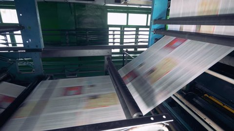 Fresh printed newspaper, magazines moving on a line at a printing office.