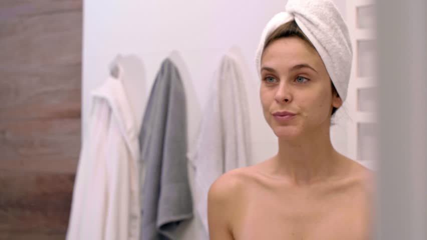 Woman touching her face and looking in the mirror after shower | Shutterstock HD Video #1015699513