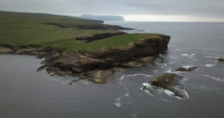 Brown cliffs of a rocky coast of Mainland, largest of Orkney islands, with bluish water of a Norwegian Sea