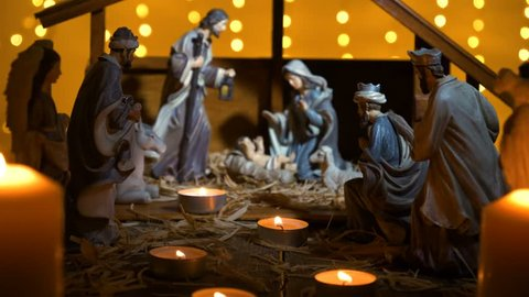 Jesus Christ Nativity scene with atmospheric lights and candles. Jesus Christ birth in a stable with Mary and Joseph figures. Christmas scene. Dolly shot 4k