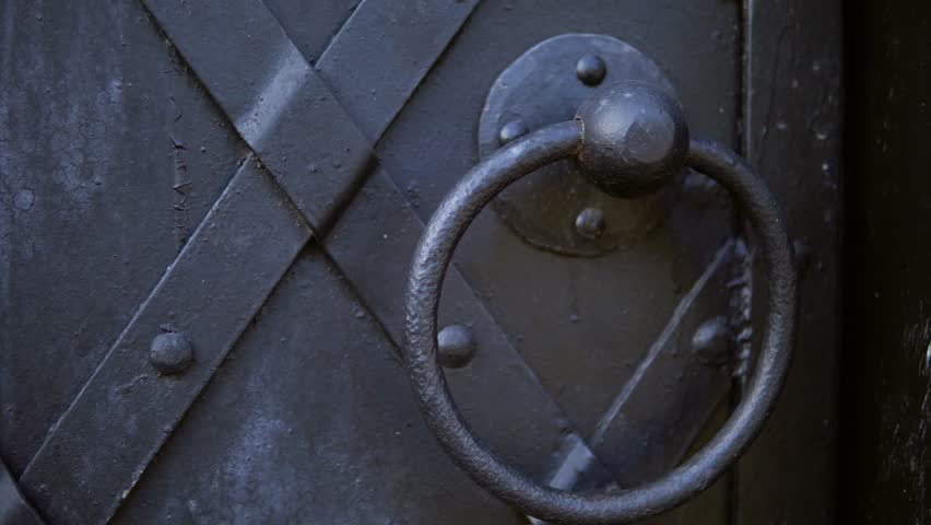 An old medieval restored black metal door reinforced with overlaid plates. The camera moves from left to right.