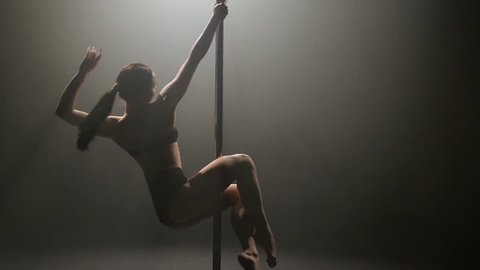 Girl is dancing poledance. Black background. Slow motion