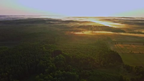 4k AERIAL: Beautiful summer morning with fog over land.