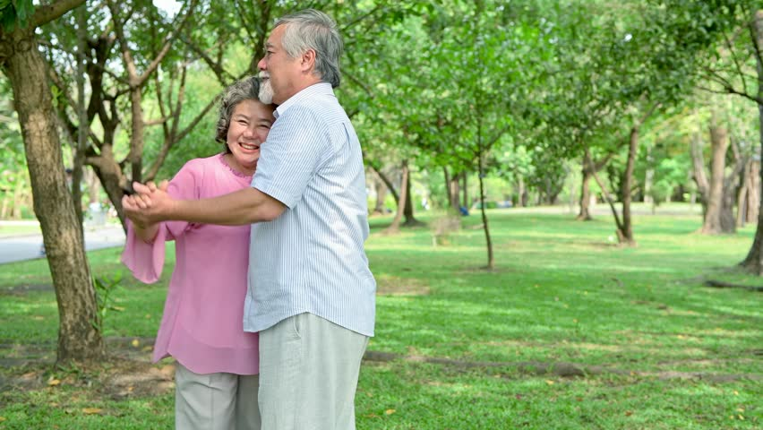 Sweet senior couple dancing in park. Old asian man and woman dancing together in park standing up. Senior lifestyle concept. | Shutterstock HD Video #1015773943