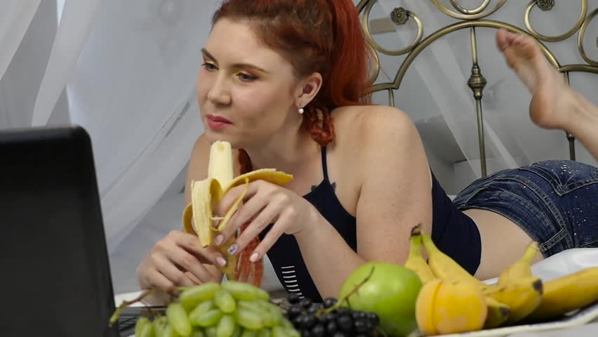 Young woman enjoying on a bed, using laptop and eating a banana at home in the morning. slow motion