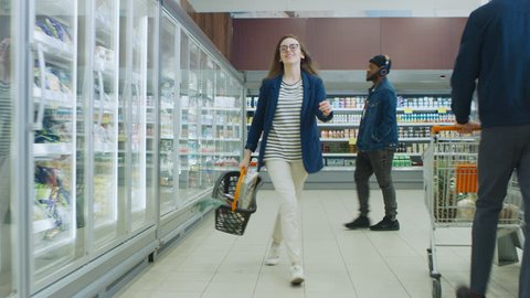At the Supermarket: Happy Young Girl Holding Shopping Basket Dances Through Frozen Goods and Dairy Products Section of the Store. Shot on RED EPIC-W 8K Helium Cinema Camera.