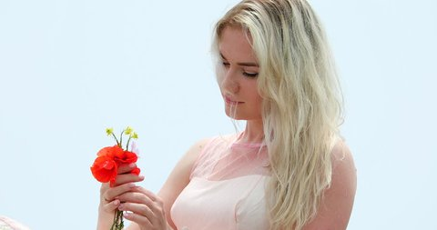 Portrait Of Beautiful Young Blond Woman In Gorgeous Pink Dress, Looking At Flower,  Wind Blowing In Her Hair. Fog Background - DCi 4K Resolution