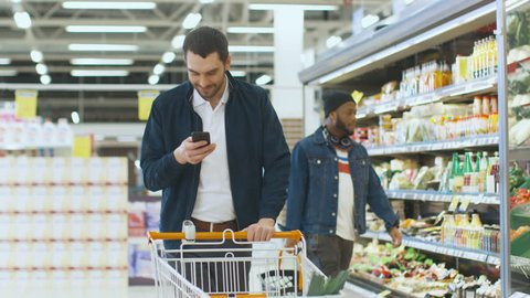 At the Supermarket: Handsome Man with Smartphone, Smiles Walks Through Fresh Produce Section of the Store, Picks up Vegetables and Throughs into Shopping Cart. Shot on RED EPIC-W 8K Helium Camera.