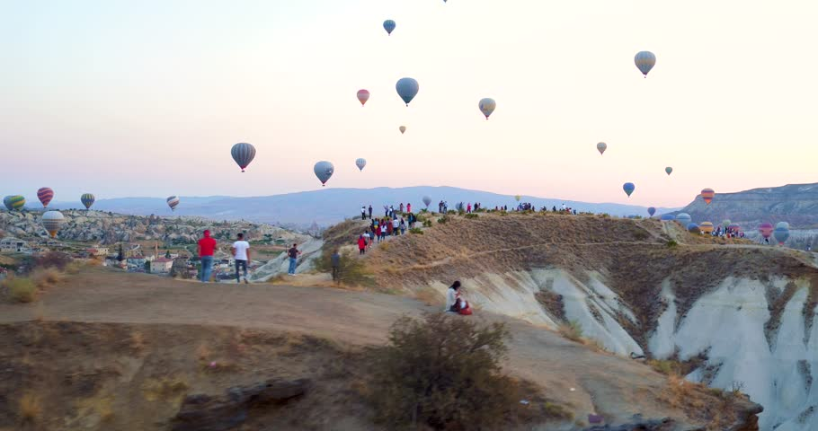People are watching stunning colourful hot air balloons flying over the valleys in famous city Cappadocia, Turkey. 4K Aerial view of Goreme.