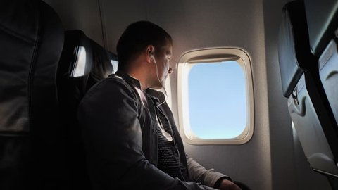 The young man looks out the window of the plane in the evening. He listens to the headphones and rests.