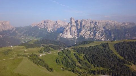 Aerial drone landscape of the meadows at high altitudes, forming gentle hills. Gardenaccia massif in the background. Dolomites, Alta Badia, Sud Tirol, Italy