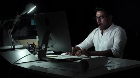Workaholic Asian businessman working on computer late at night in the office feeling tired, sleepy and having neck pain from overwork