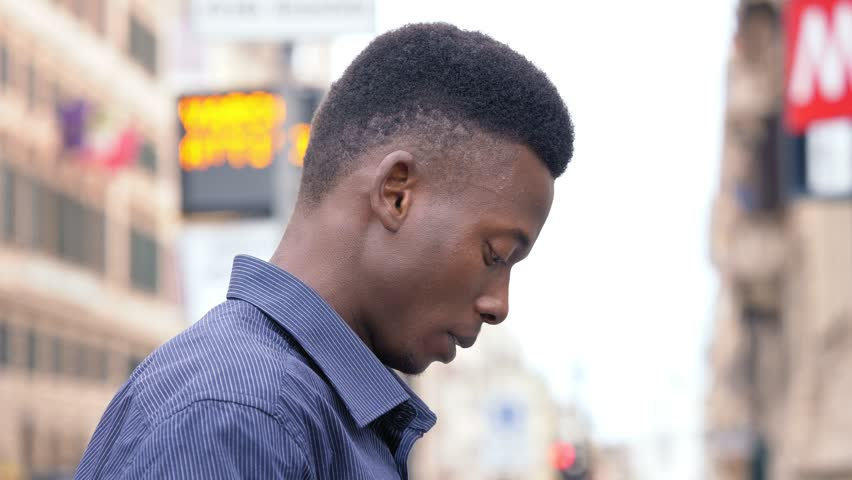 Attractive young black man in the city, focused on typing on smart phone | Shutterstock HD Video #1015848133