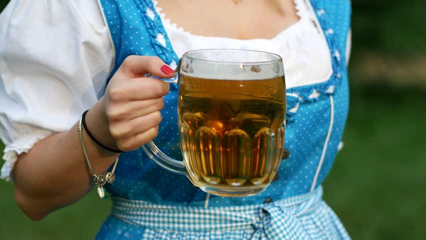 Young woman in blue bavarian dirndl celebrating oktoberfest. Close up