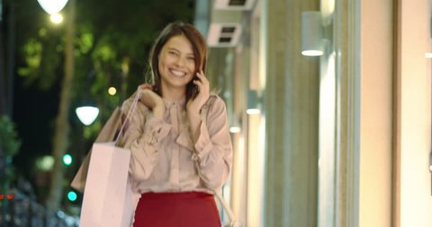Girl walking down broadway near mall with shopping bags in hands, talking on phone and happily smiling 4k