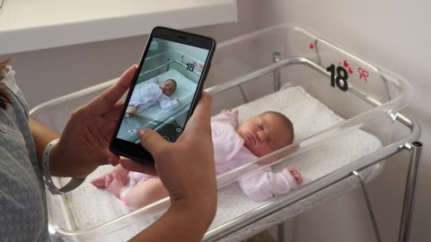 Take mobile phone pictures young mother of her newborn child sleeping in maternity hospital bed