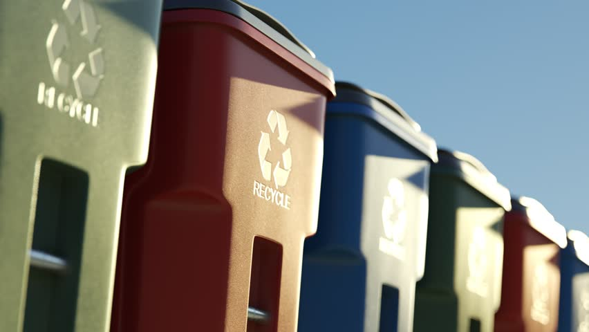 Colorful, plastic garbage bins, with recycle logo on the front, stacked in a row against a clear blue sky background in an endless, loop. Symbol of recycling, waste sorting and saving the environment.