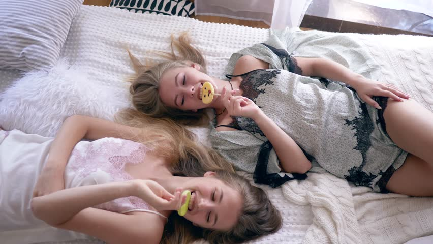 hen party, sisters in silk sleepwears eat sweet lollipops and talk lying on the bed at home