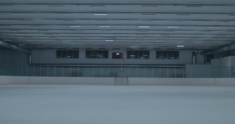 WIDE EST Lights are turning on on an empty ice hockey training rink, no players. 4K UHD