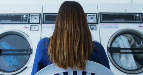 Rear view of woman sitting on chair at laundromat 4k