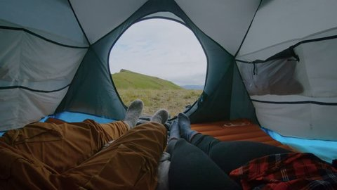 Cute and in love couple lay in camping tent in authentic hipster wool socks enjoy view from inside on green nature forest and field. Drink coffee from hiking mug, nomad adventure millennial lifestyle