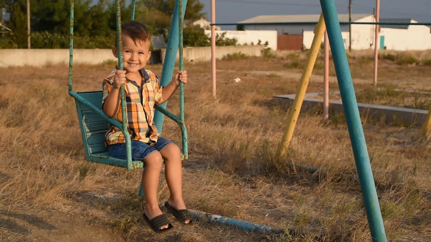 Baby on swing swinging one near the sea, in shirt and denim shorts