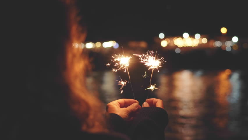 A young red-haired woman stands at the seaside on the pier and holds burning lit Christmas bengal lights and meets the new year against a bright background of bokeh large lights #1015950583