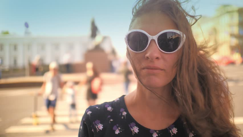 Young beautiful brunette woman in sunglasses looking at camera, crowd of people on summer city street in background. Closeup, shallow DOF, slow motion, 4K UHD.   Shutterstock HD Video #1015951933