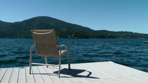 An empty chair sitting on a dock at Hayden Lake, Idaho. Peaceful lapping of the water makes for a relaxing summer day.