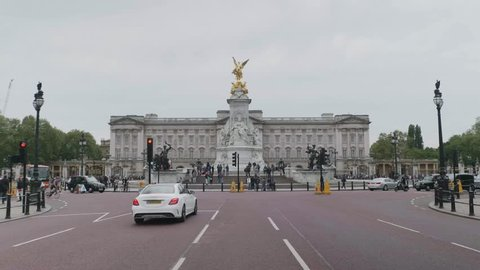 A 4K wide-shot of the traffic in front of the Buckingham Palace in London, administrative headquarters of the monarch of the United Kingdom.