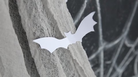 Halloween holidays decoration for party. Cute not scary paper white bat and word Boo written with crayons on black balckboard background. Real time full hd video footage.