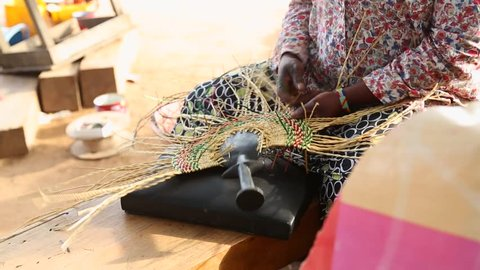 African Art. A woman weaves a fan in a marketplace in Ghana.