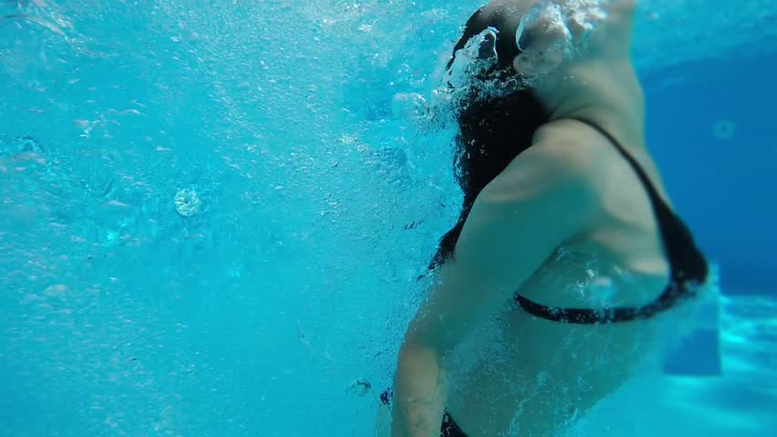 An original view of a young woman jumping in the pool and shot underwater. She sends many bubbles up, looks frightened and funny in slo-mo | Shutterstock HD Video #1016052523