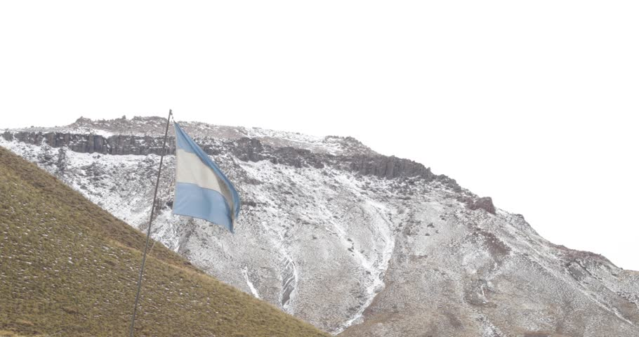 Argentinian weathered flag flowing and moving on a windy gray cloudy day with mountains with snow on the bakground. Mendoza, Argentina.