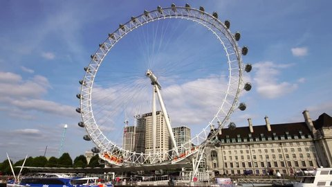 Low angle moving shot of London Eye ferris wheel over Thames River in London Great Britain