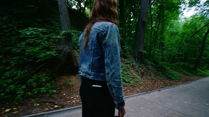 Young woman riding a gyro in the park. Around the trees. People walk. | Shutterstock HD Video #1016111473