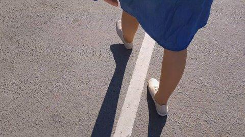 women's feet in sneakers are on the asphalt.