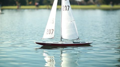 Remote controlled yacht being raced on a pond, slow motion