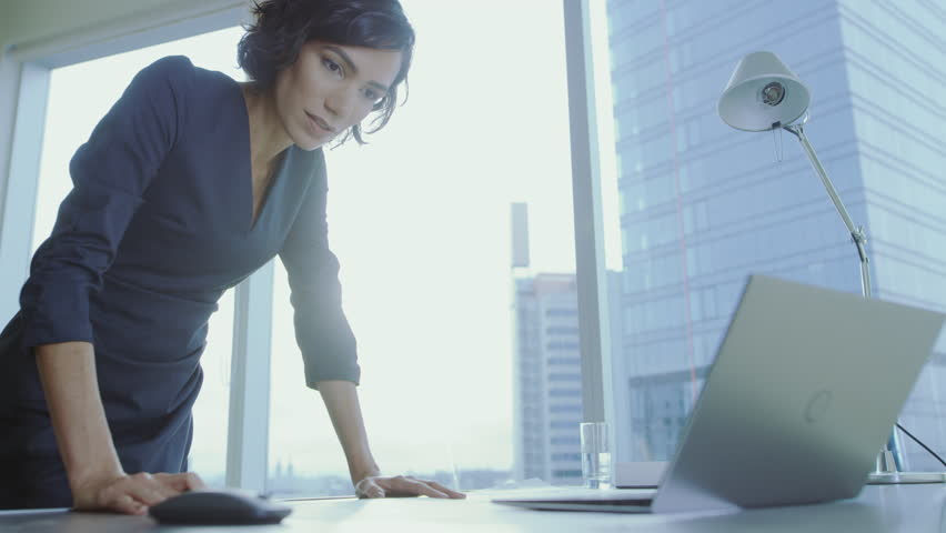Low Angle Shot of Confident Businesswoman Leans on Her Office Desk, Writes Down Information in Documents and Looks at Laptop. Successful Woman Doing Business. Shot on RED EPIC-W 8K Helium Camera. | Shutterstock HD Video #1016145733