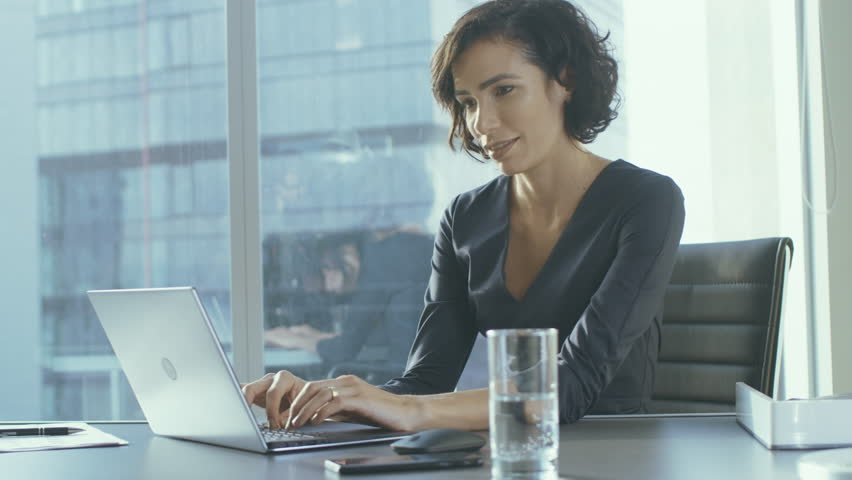 Confident Female Executive Works on a Laptop Sitting at Her Desk in Modern Office with Big City View. Smiling Successful Busiesswoman Uses Laptop. Shot on RED EPIC-W 8K Helium Cinema Camera. | Shutterstock HD Video #1016145823