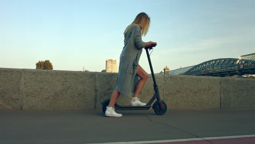 Attractive woman stands, scoots and rides on the electric kick scooter