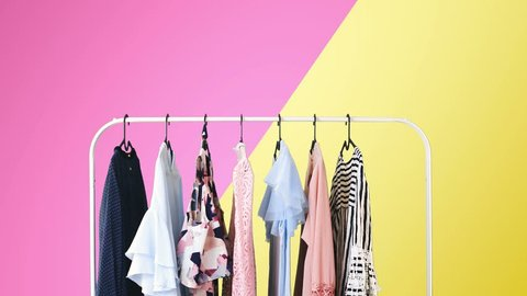 Women's clothing on a white clothes hanger on violet and yellow pastel colors background.