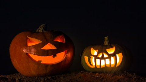 Two pumpkins with candles inside. Time laps. Night sky, full moon. Holiday Halloween.