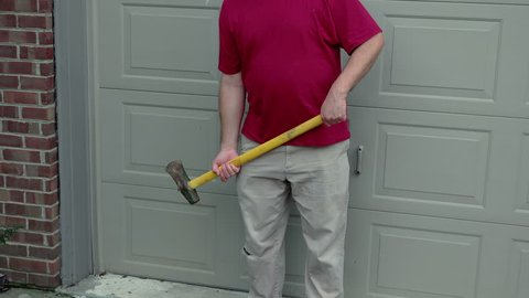 Man with a sledge hammer being threatening