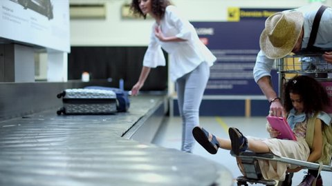 WS Woman picking up wheeled luggage from baggage claim at East Midlands Airport while father and daughter (8-9) using digital tablet / Derby, Derbyshire, UK
