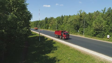 Beautiful top view motion over modern road with driving red tipper truck among green forests on sunny day