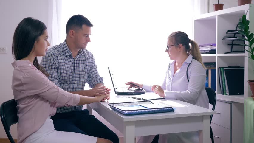 Young family visiting a doctor, a physician consults a couple about fertility sitting at the desk in the medical office | Shutterstock HD Video #1016211433
