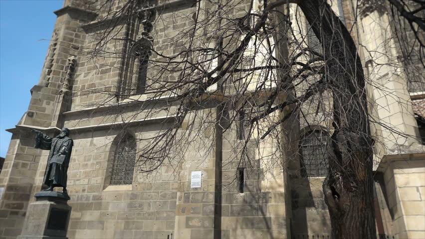 Footage of gothic architecture, The Black Church in Brasov, Romania, Johannes Honterus statue, tilt